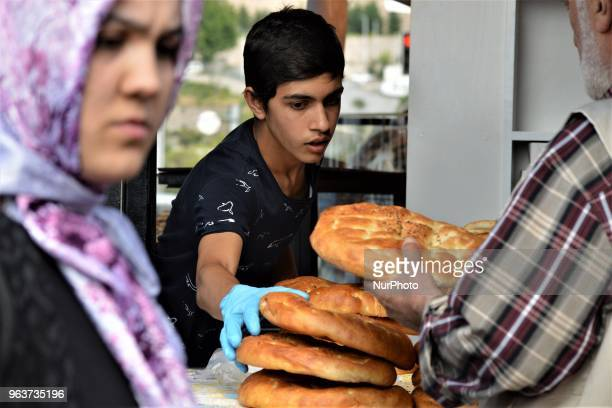 A young vendor places traditional Ramadan bread on a counter in a bazaar during the Muslim holy fasting month of Ramadan in the historic Ulus...