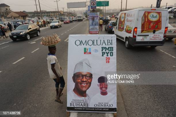 A young vendor walks past campaign poster of candidate of the ruling All Progressives Congress Nigerian President Mohammadu Buhari and Vice President...