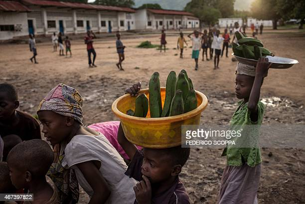 Young vendors carry their wares on their heads as they walk along a street in the village of Baraka South Kivu on March 23 2015 AFP PHOTO/FEDERICO...
