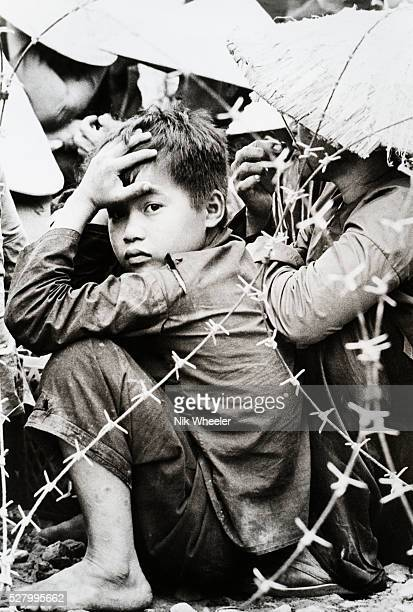 A young Vietnamese boy arrested during anti government demonstration in Danang South Vietnam during the VietnamWar stares out from behind barbed wire