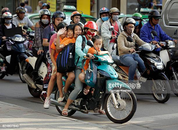 A young Vietnamese girl drives with three children on a scooter through the city in Ho Chi Minh City A girl is waving at the camera on November 01...