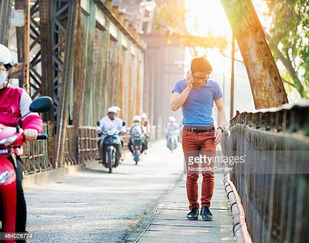Young Vietnamese man crossing Long Bien Bridge talking on phone