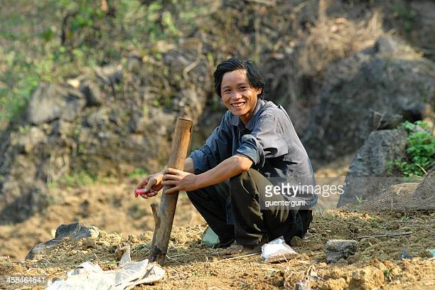 Young Vietnamese Man is smoking a traditonal pipe