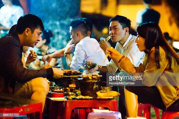 Young Vietnamese people enjoying barbecue on Hanoi street late night