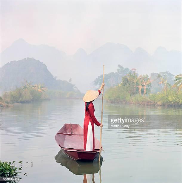 Young Vietnamese woman piloting gondola in river