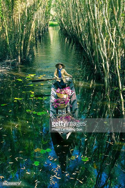 Young Vietnamese woman rowing boat loaded flowers