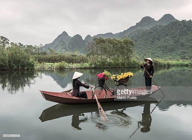 young Vietnamese women rowing boat along the Perfume river