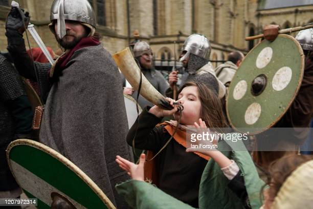 A young Viking reenactor blows a horn as he waits to march through York as part of the 36th York Viking Festival on February 22 2020 in York England...