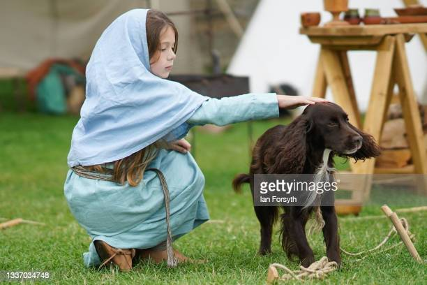 Young Viking re-enactor pets a dog as she sits in camp in the grounds of Whitby Abbey on August 29, 2021 in Whitby, England. Around 130 re-enactors...