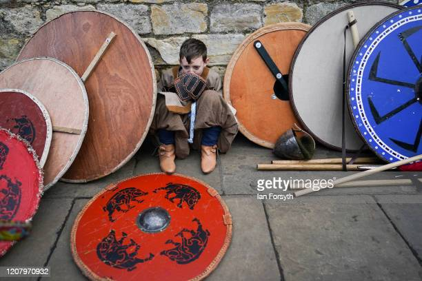 A young Viking reenactor sits among shields as he waits to march through York during a living history display as part of the 36th York Viking...
