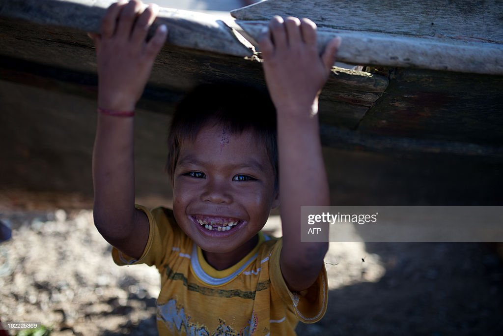 A young villagers smiles as he plays in Tanjung Labian, near the location where suspected Philippine militants are holding off on February 21, 2013. Followers of a Philippine sultan who crossed to the Malaysian state of Sabah this month will not leave and are reclaiming the area as their ancestral territory, the sultan said on February 17 amid a tense stand off.