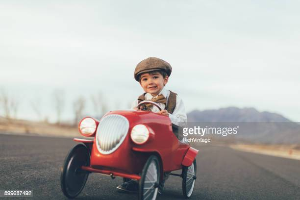 Young Vintage Boy Drives Toy Car