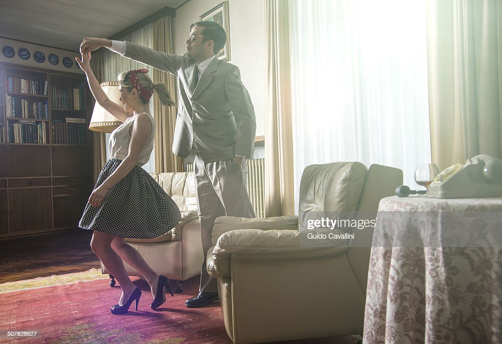 Young vintage couple dancing rock n roll in sitting room : Stock Photo