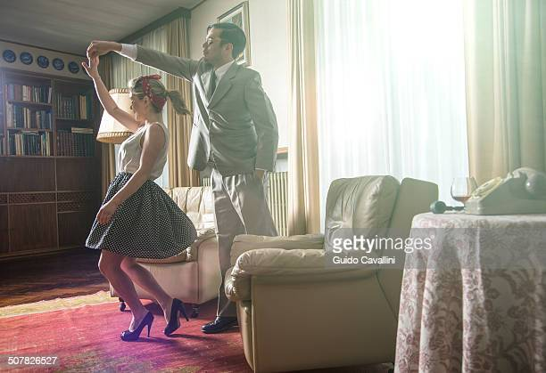 young vintage couple dancing rock n roll in sitting room - freaky couples stock photos and pictures