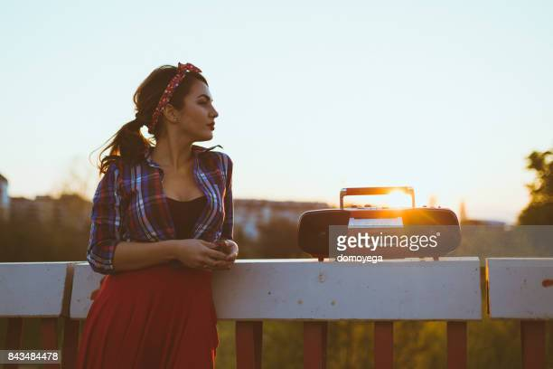 Young vintage styled woman listening to music outdoors