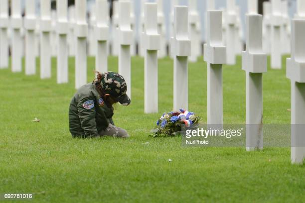 Young visitor seats in front of one of the graves of fallen soldiers at the Normandy American Cemetery that contains the remains of 9,387 American...