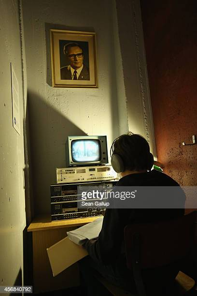 A young visitor sits at a reconstructed Stasi secret police surveillance corner under a portrait of former East German communist leader Erich...