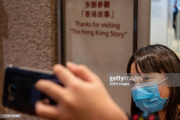 """Young visitor takes a selfie at the exit of the museum with a message displayed on a board """"Thanks for visiting The Hong Kong story"""" during the last..."""
