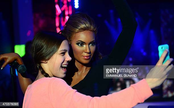 A young visitor takes a selfie with a wax figure of singer Beyonce during the launch of an interactive music experience exhibition at Madame Tussauds...