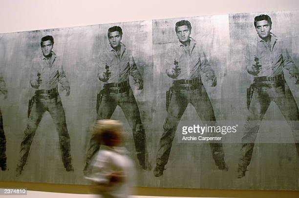 A young visitor to the Andy Warhol Museum in Pittsburgh walks past the Elvis silk screen painting on August 6 2003 Pittsburgh Pennsylvania The Museum...