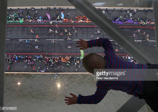 A young visitor to Tower Bridge's Exhibition glass walkway watches runners on The Virgin Money London Marathon cross the River Thames on April 26...