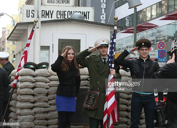 Young visitors from Russia pose for a photo with an actor dressed as a US soldier at the former Checkpoint Charlie order crossing between West and...
