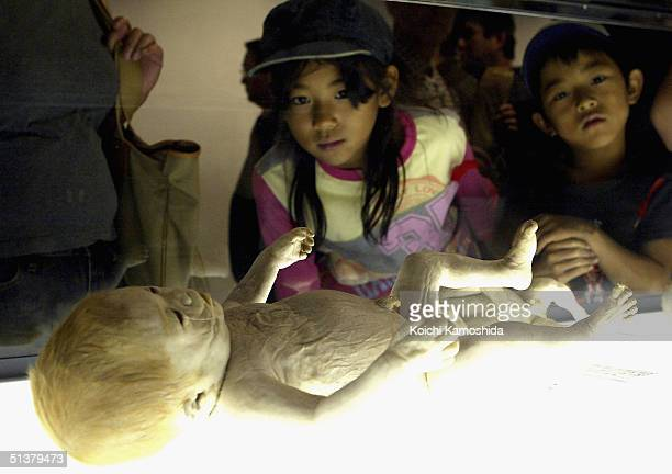 Young visitors gaze at a preserved plastomic foetus at the Mysteries of the Human Body exhibition which displays some 170 specimens on October 1 2004...
