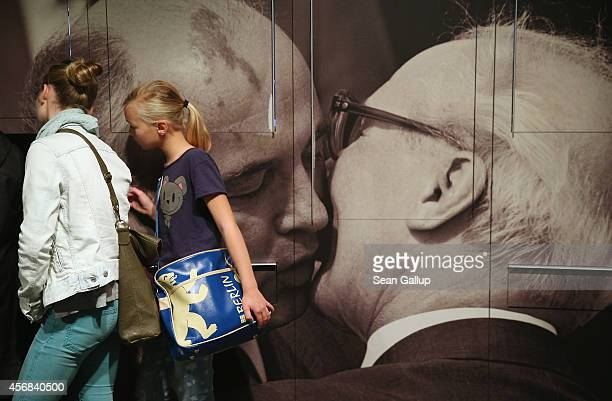 Young visitors look at an exhibit next to a photograph of former Soviet leader Mikhail Gorbachev embracing former East German communist leader Erich...