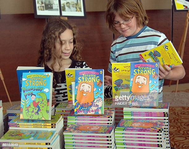 Young visitors look at childrens books by British author Jeremy Strong during the International Festival of Literature in Dubai on February 28 2009...