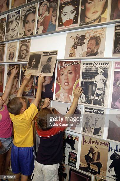 Young vistors to the Andy Warhol Museum explore the wall of Interview magazine covers on August 6 2003 Pittsburgh Pennsylvania The Museum in...