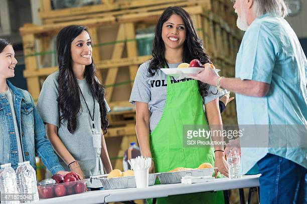 young volunteers are serving meals to seniors in food bank - depression bread line stock pictures, royalty-free photos & images