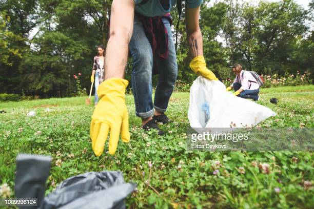 young volunteers collect garbage in a public park - humanitarian aid stock pictures, royalty-free photos & images