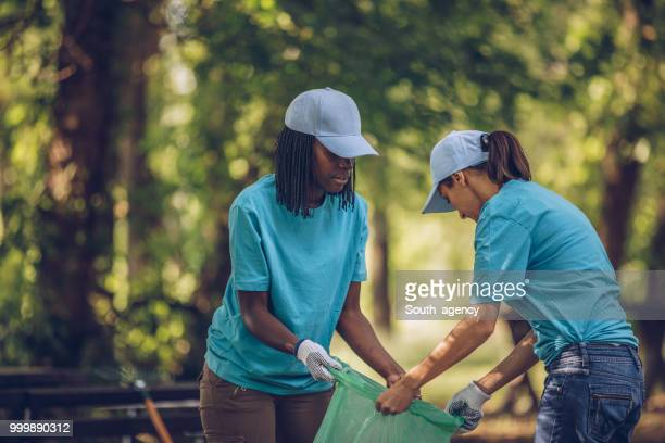 young volunteers picking up trash - community volunteer stock pictures, royalty-free photos & images