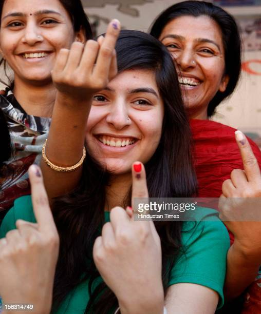 Young voters show off their marked fingers after casting their votes in the first phase of Gujrat state assembly elections on December 13 2012 in...