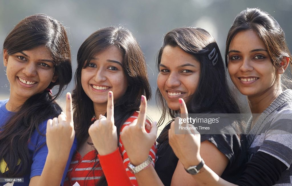Young voters show off their marked fingers after casting their votes in the first phase polling of Gujarat assembly election on December 13, 2012 in Surat, India.