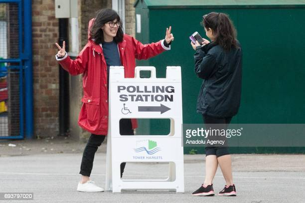Young voters take photos next to a polling station sign at John Scurr Primary School polling station after voting in the General Election in London...