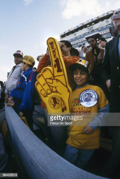 A young Wahington Redskins fan holds up his gigantic foam hand gesturing to the team during Super Bowl XVIII featuring the Washintgon Redskins and...