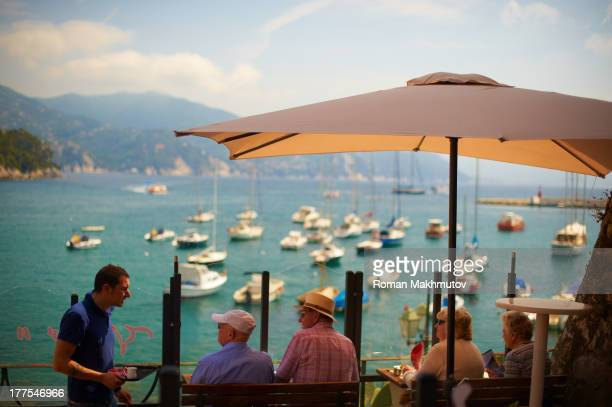 CONTENT] Young waiter serving group of seniors They are sits in cafe in front of lagoon filled with yachts