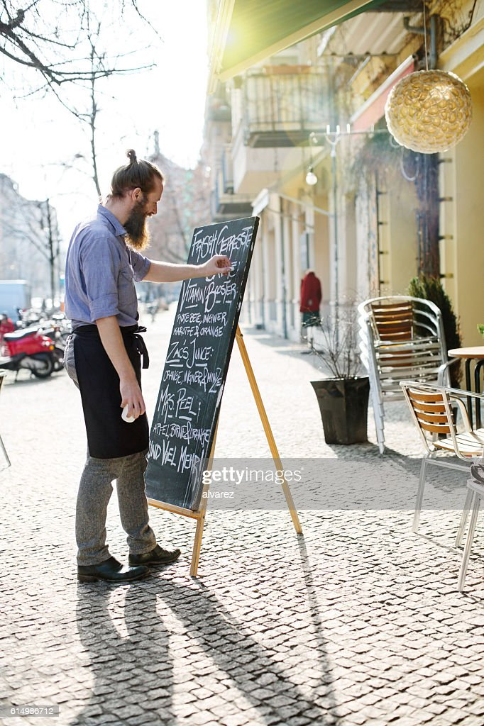 Young waiter updating todays special menu board : Stock Photo