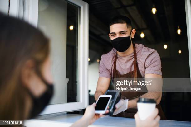 young waiter with face mask and gloves serving coffee through coffee shop window, contactless payment concept. - paying stock pictures, royalty-free photos & images