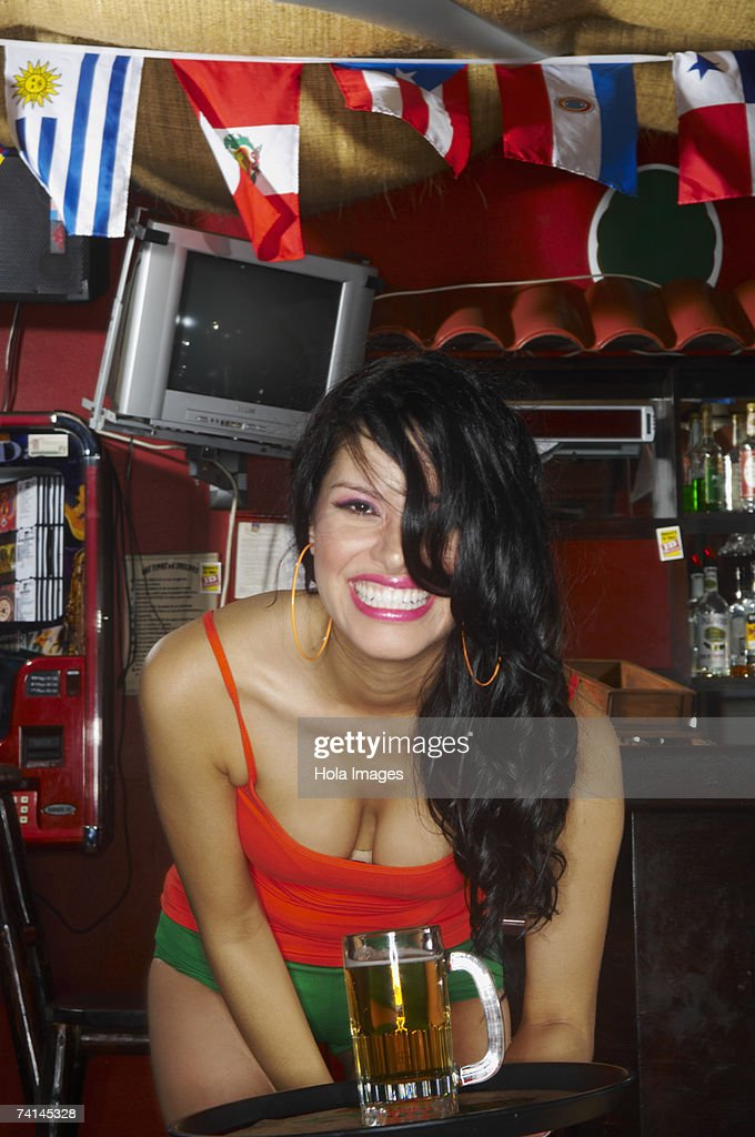 Young waitress carrying tray laughing