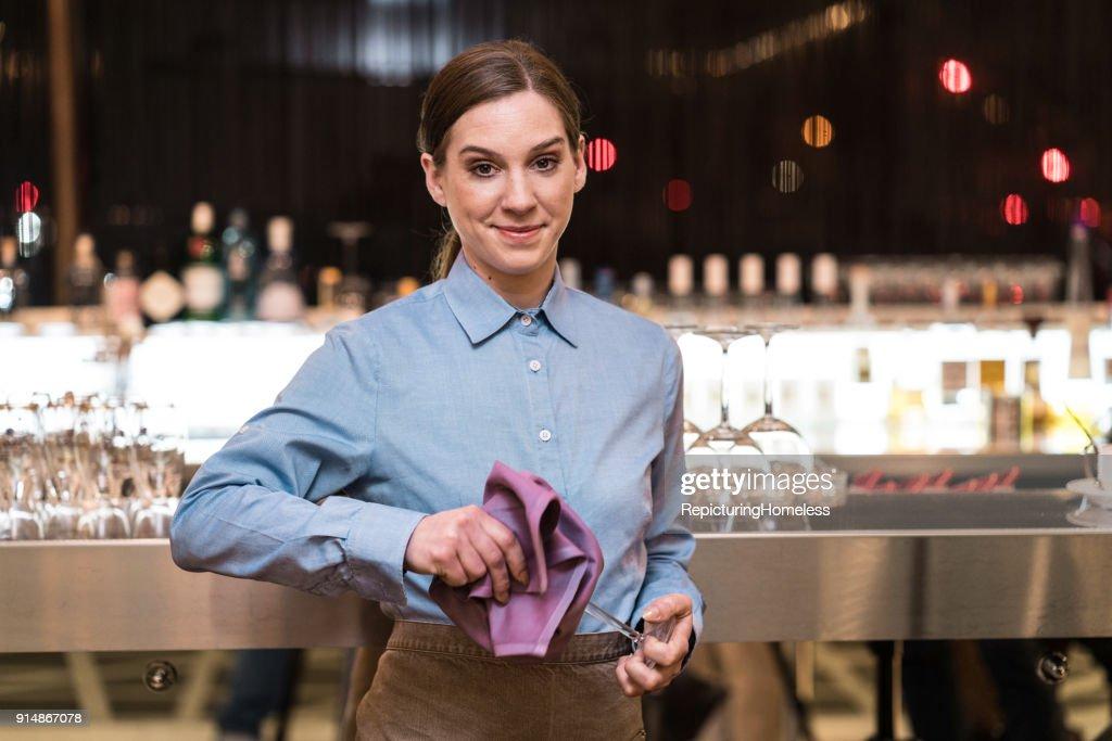 Junge Kellnerin putzt ein Weinglas und schaut in die Kamera : Stock-Foto