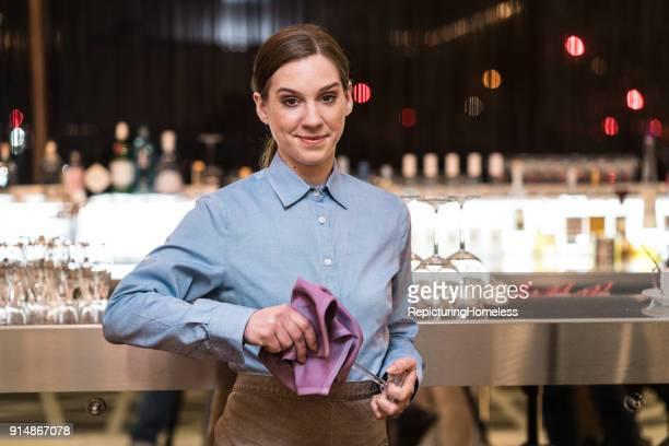 Junge Kellnerin putzt ein Weinglas und schaut in die Kamera