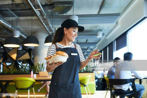 young waitress delivers food in restaurant - wait staff stock pictures, royalty-free photos & images
