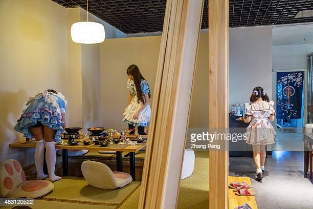 Young waitress dressed up as Japanese cartoon characters are cleaning the table A cosplay theme restaurant in Sanlitun Soho is a popular social place...