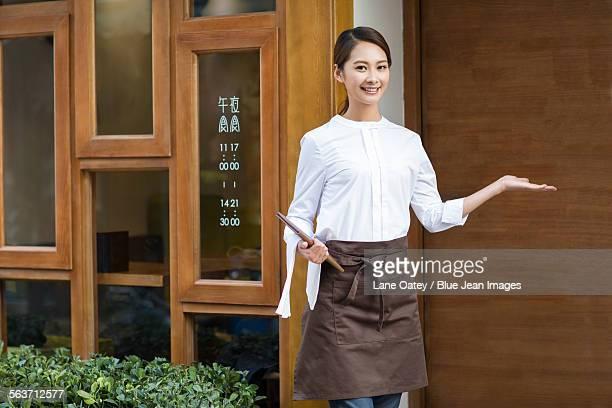 Young waitress greeting in restaurant doorway
