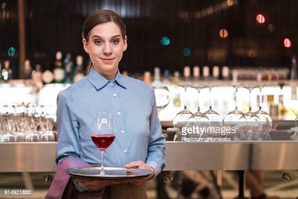 Junge Kellnerin hält ein Tablett mit einem Weinglas
