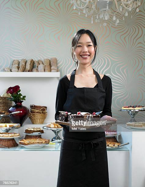 Young waitress holding tray of desserts, smiling, portrait