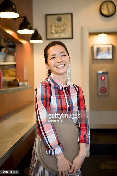 young waitress in café, holding tray