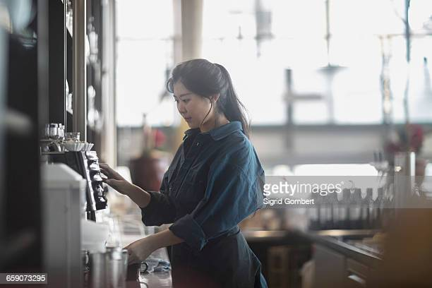 Young waitress making coffee in coffee shop, Freiburg Im Breisgau, Baden-württemberg, Germany